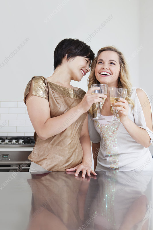 Laughing women toasting each other
