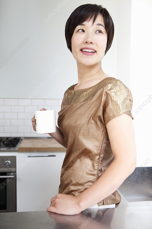 Woman drinking cup of coffee in kitchen
