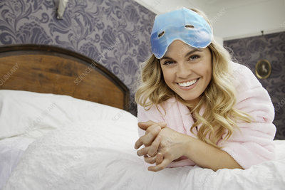 Woman on bed with eye mask on forehead