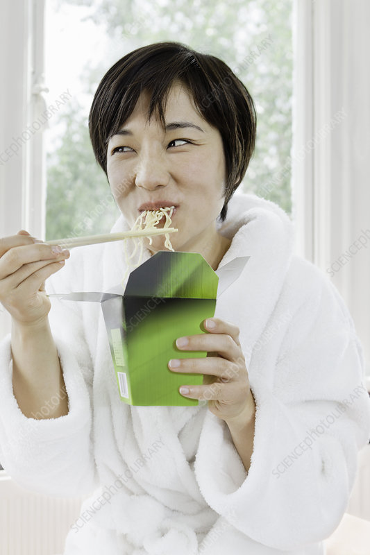Woman in bathrobe eating Chinese food