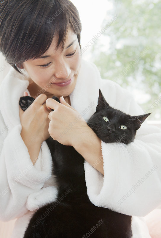 Woman in bathrobe holding cat
