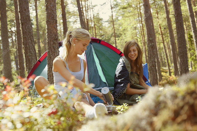 Women setting up campsite in forest