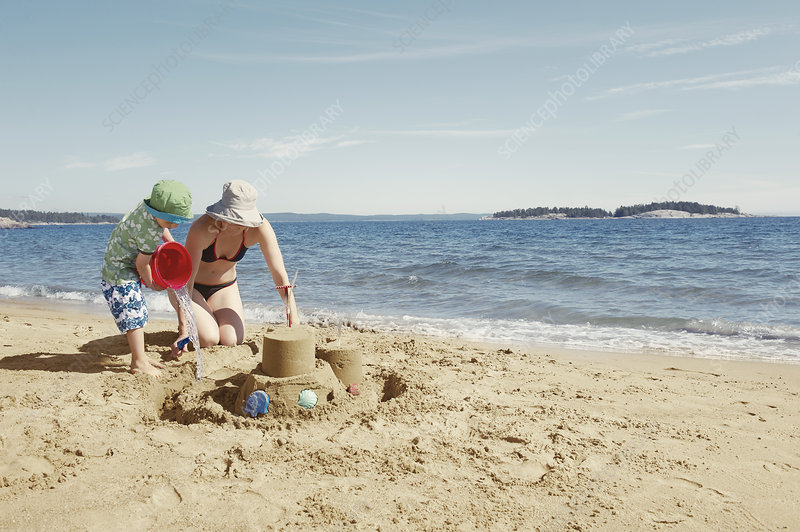 Mother and child building sandcastle