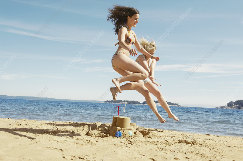 Women jumping over sandcastle