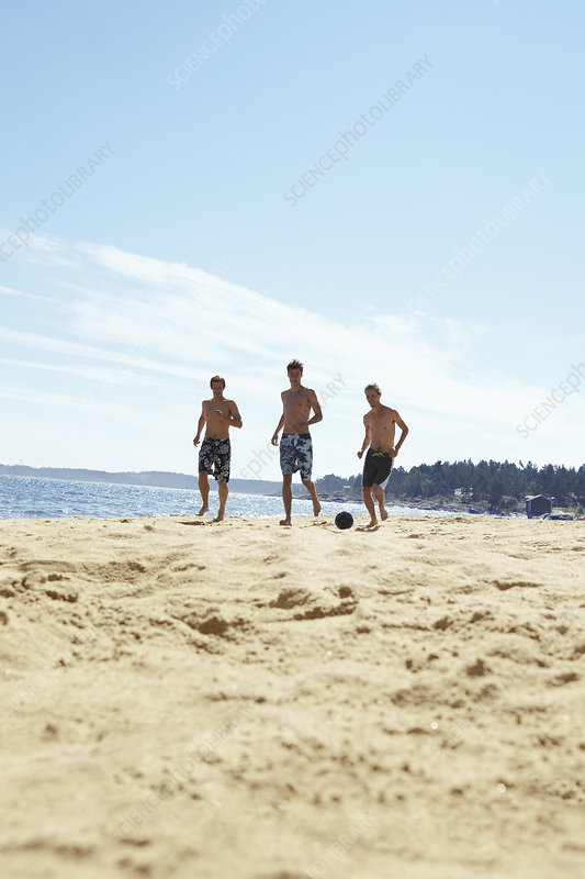 Men playing soccer on beach
