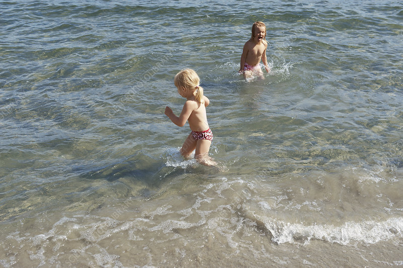 Children playing in waves on beach