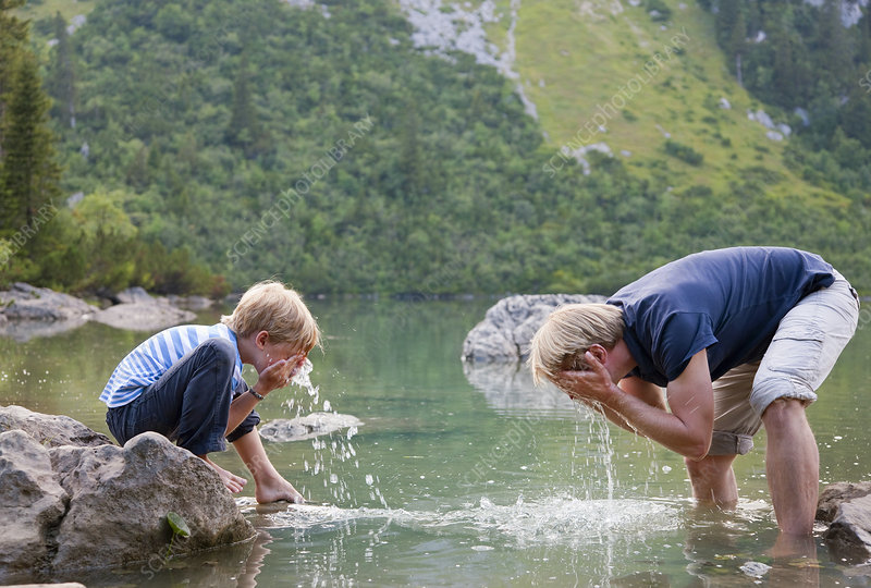Boy washing his face in still lake