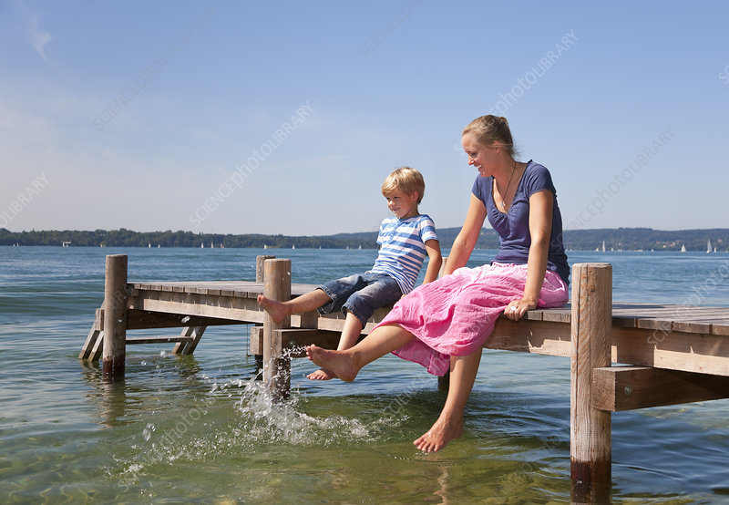 Mother and daughter dipping feet in lake