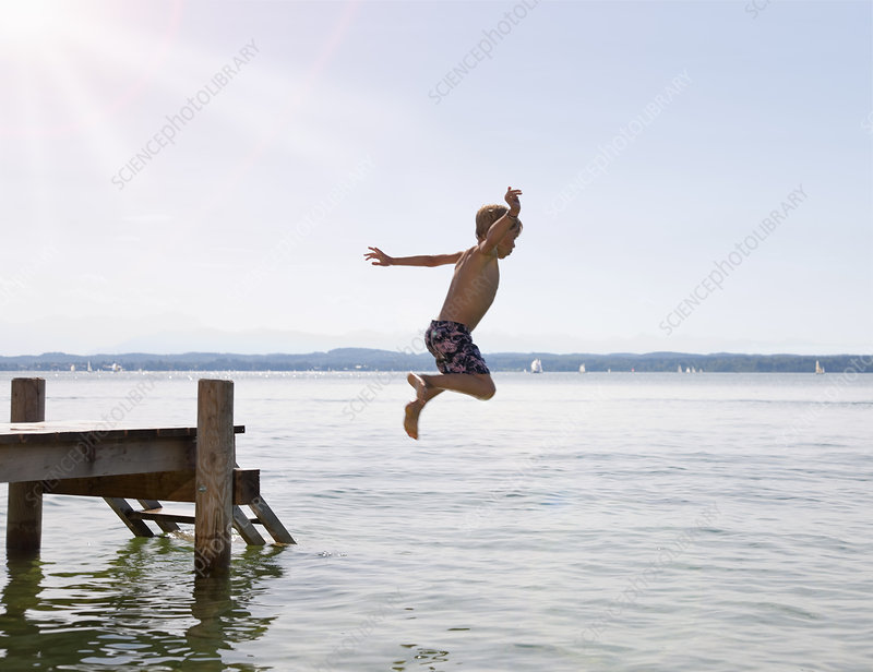 Boy jumping into lake from dock