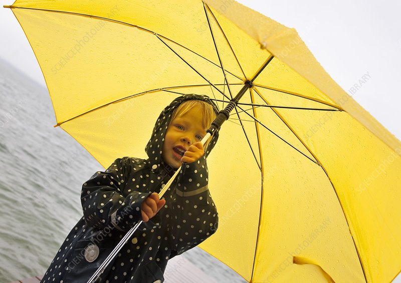 Girl holding yellow umbrella by lake
