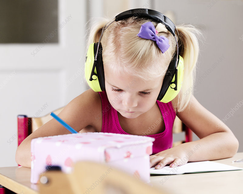Girl listening to headphones at desk