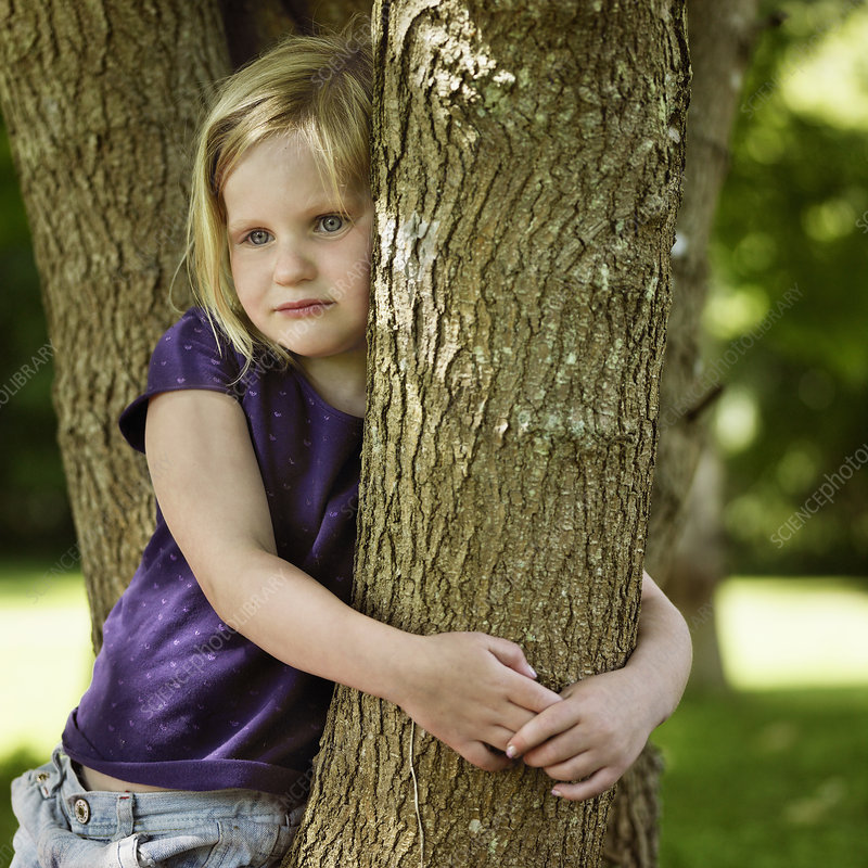 Smiling girl hugging tree