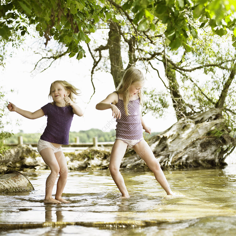 Smiling girls playing in lake
