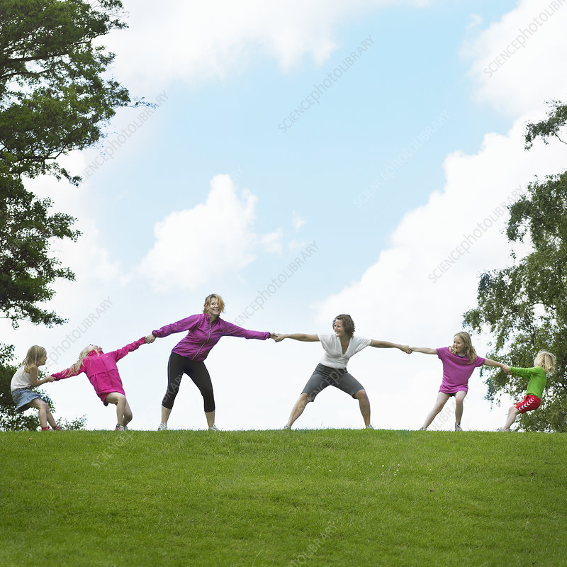 Girls playing tug-of-war in field