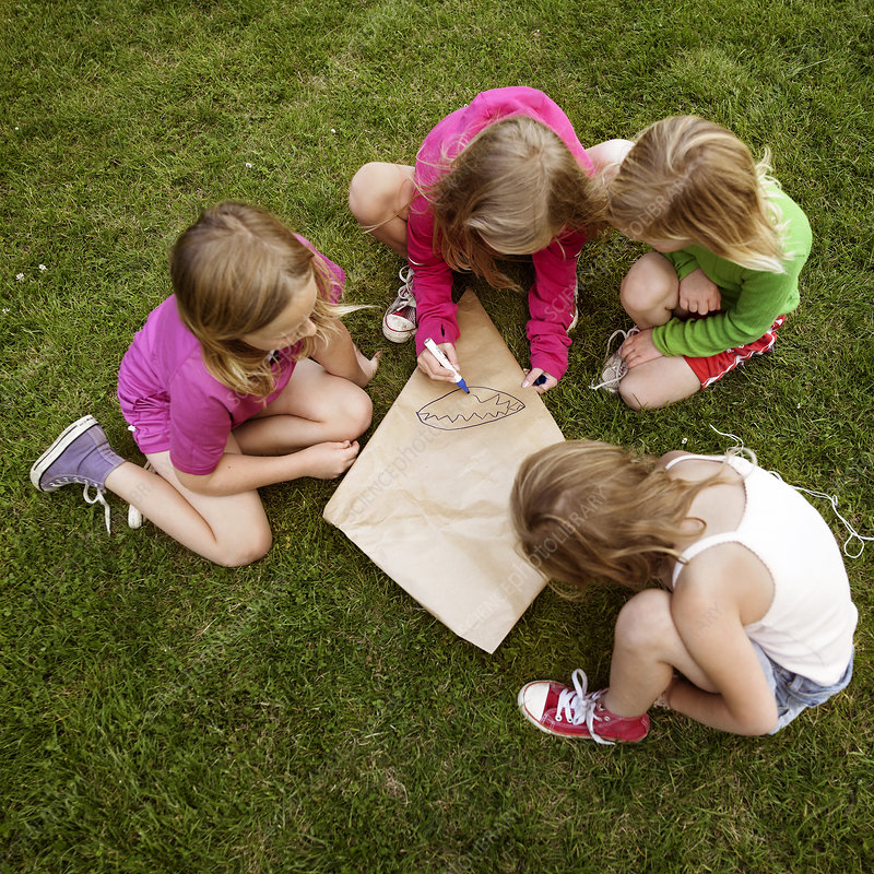 Girls making a kite in grass
