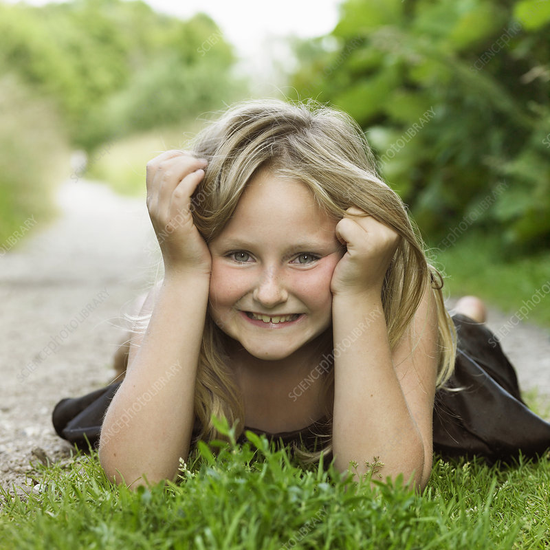 Girl laying on grass in dirt path