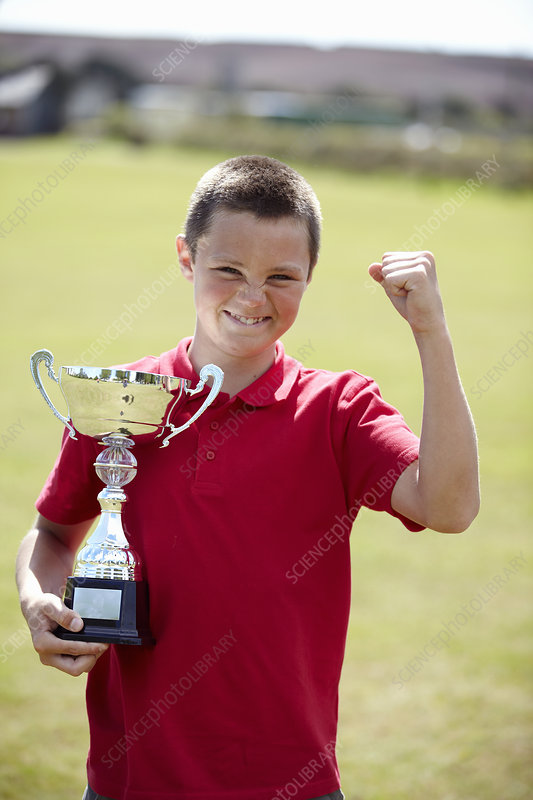 Boy cheering with trophy outdoors