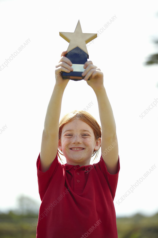 Girl cheering with trophy outdoors