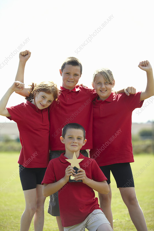 Children cheering with trophy outdoors