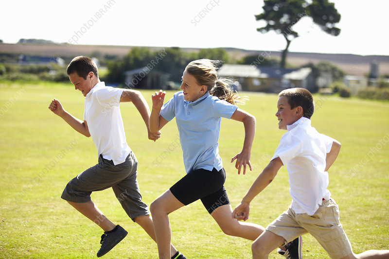 Smiling children racing in field