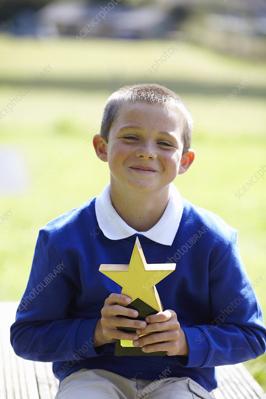 Smiling boy holding trophy outdoors