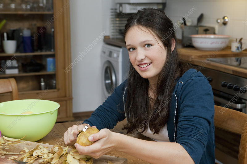 Girl peeling potatoes in kitchen