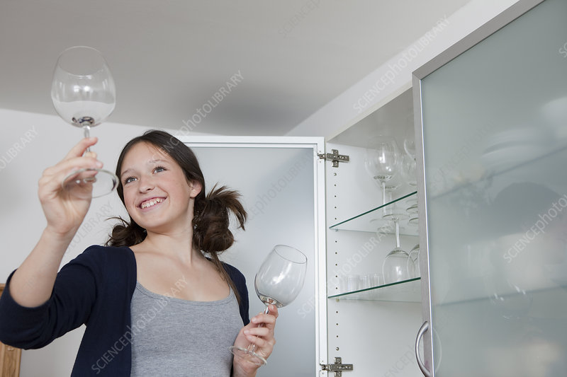 Smiling girl putting away wine glasses