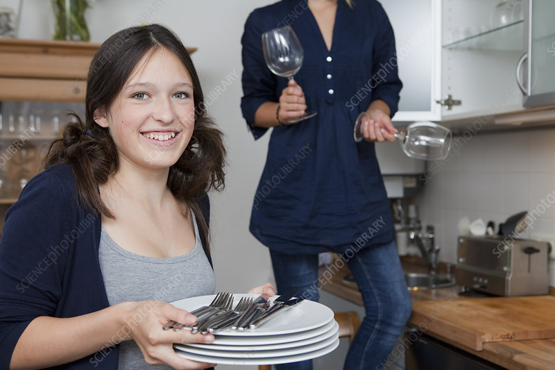 Smiling girls putting away dishes