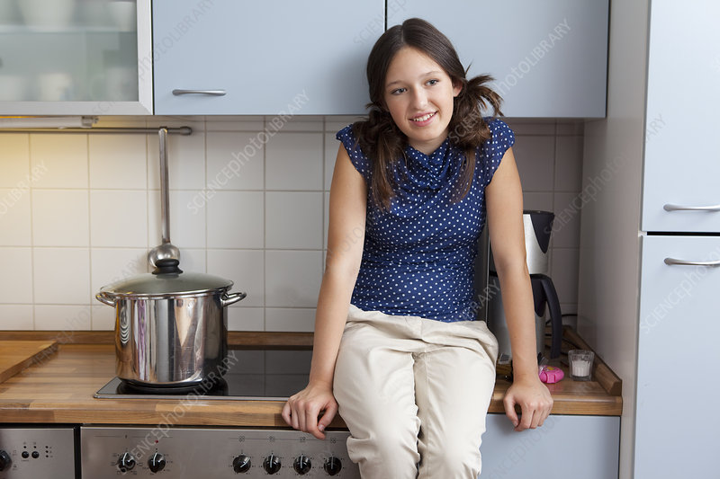 Smiling girl cooking in kitchen