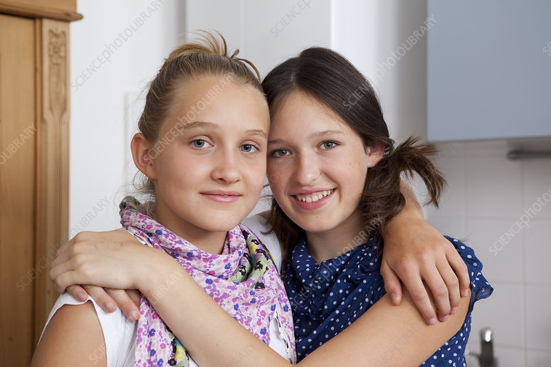 Smiling girls hugging in kitchen