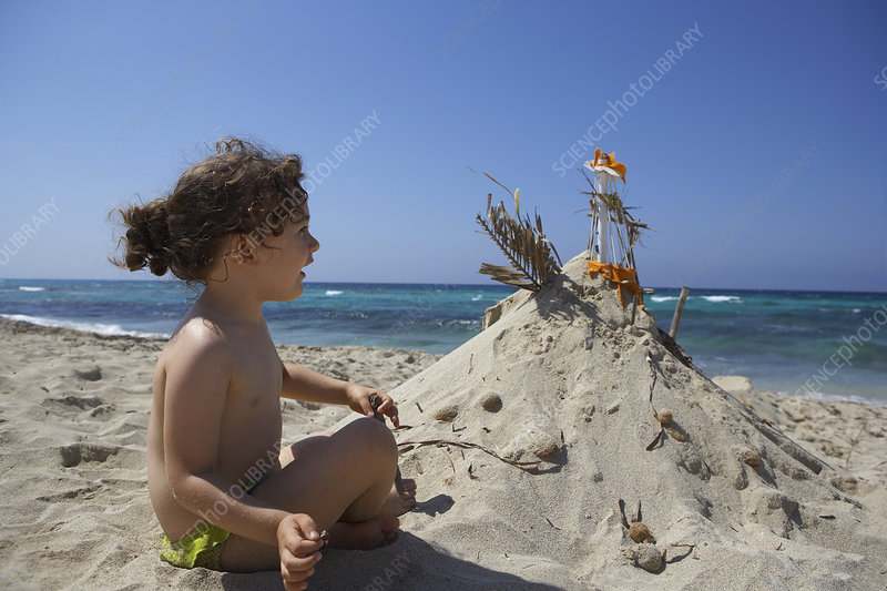 Girl building sandcastle on beach