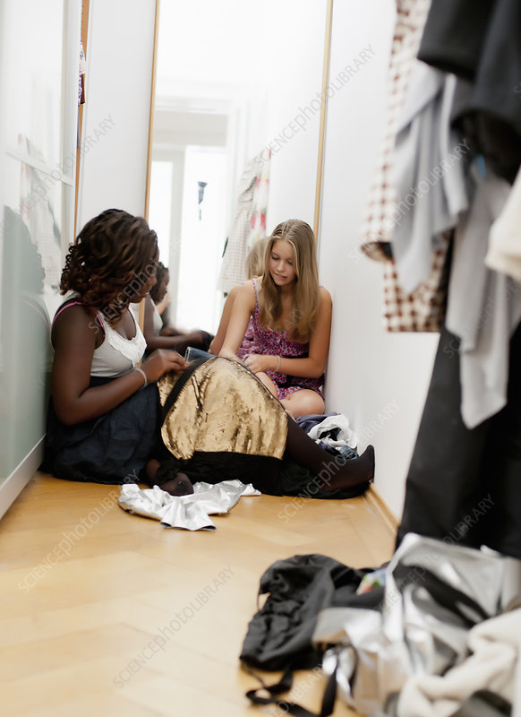 Teenagers picking out clothes in closet