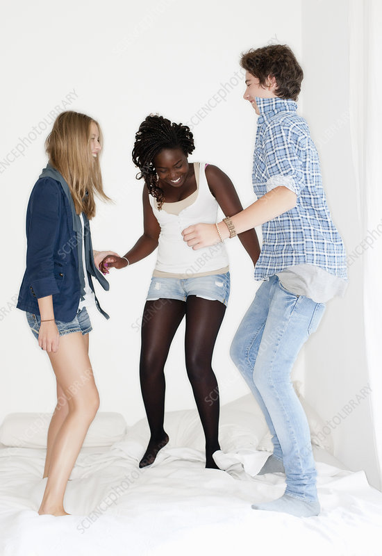 Teenagers jumping on bed