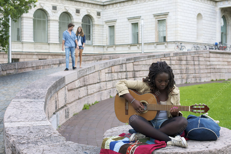 Teenage girl playing guitar on campus