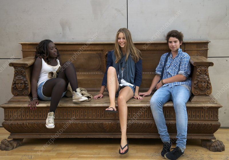 Teenagers relaxing on ornate bench