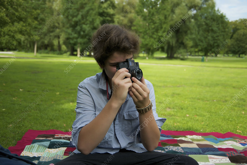 Teenage boy taking pictures in park