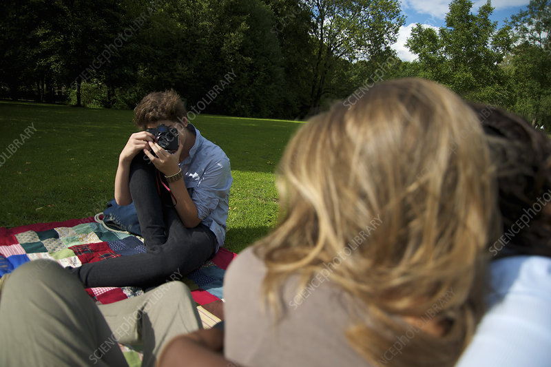 Boy taking pictures of friends in park