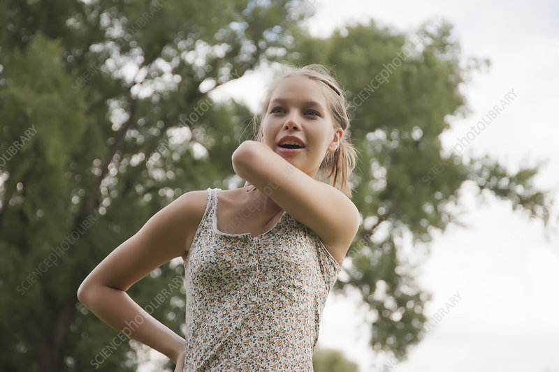 Teenage girl rubbing her neck in park - Stock Image - F004
