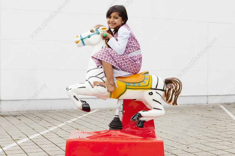 Girl riding mechanical horse outdoors