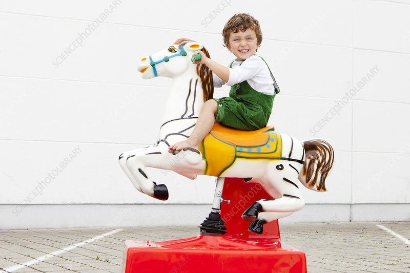 Boy riding mechanical horse outdoors