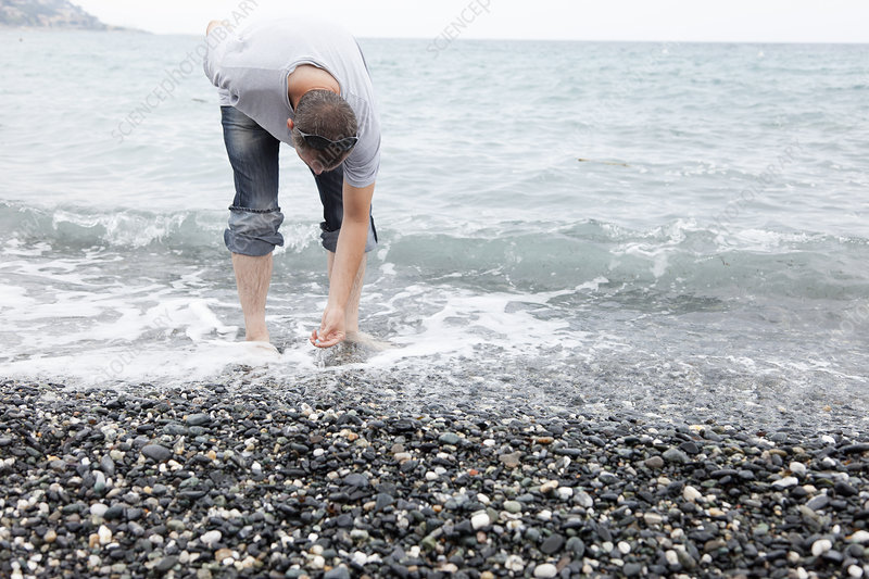 Man collecting pebbles on rocky beach