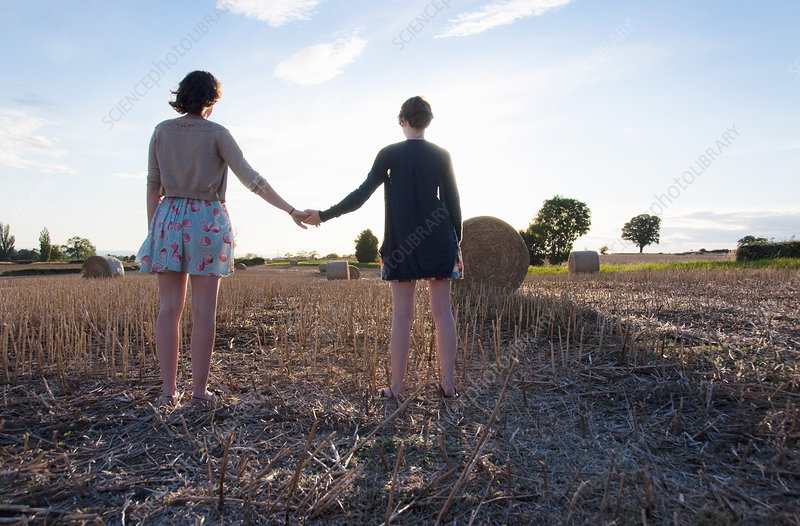 Girls holding hands in hay field