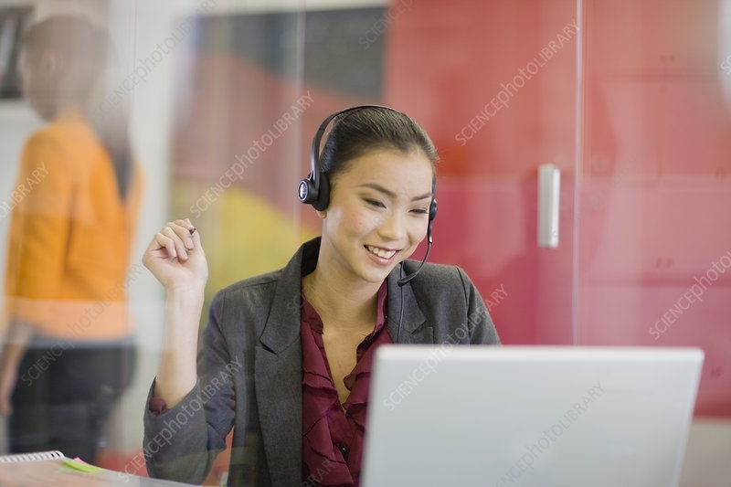 Businesswoman on headset using laptop
