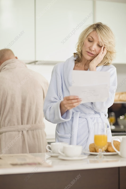 Stressed woman reading mail in bathrobe