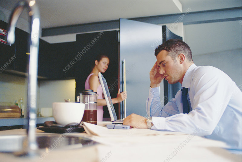 Businessman using laptop in kitchen