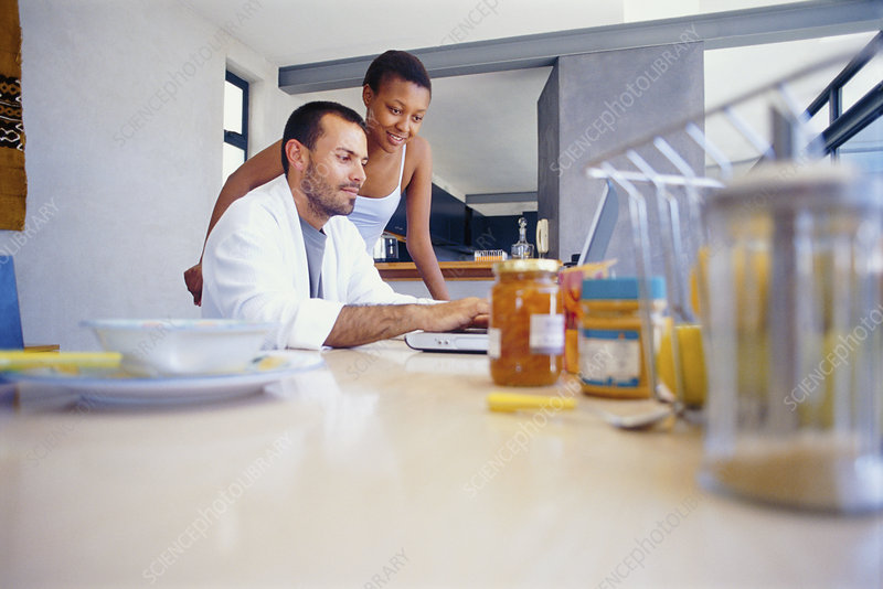 Couple using laptop at breakfast table