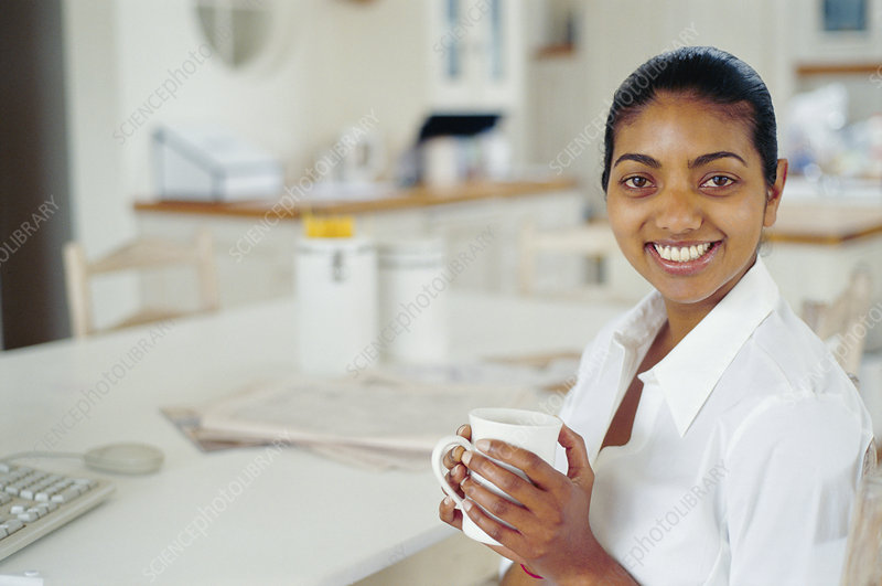 Woman having cup of coffee at computer
