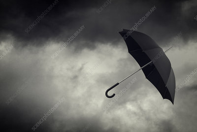 Umbrella floating in stormy sky