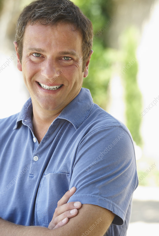 Smiling man standing with arms folded