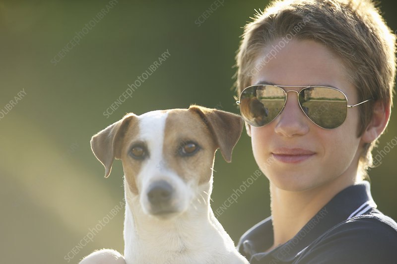 Teenage boy holding dog outdoors